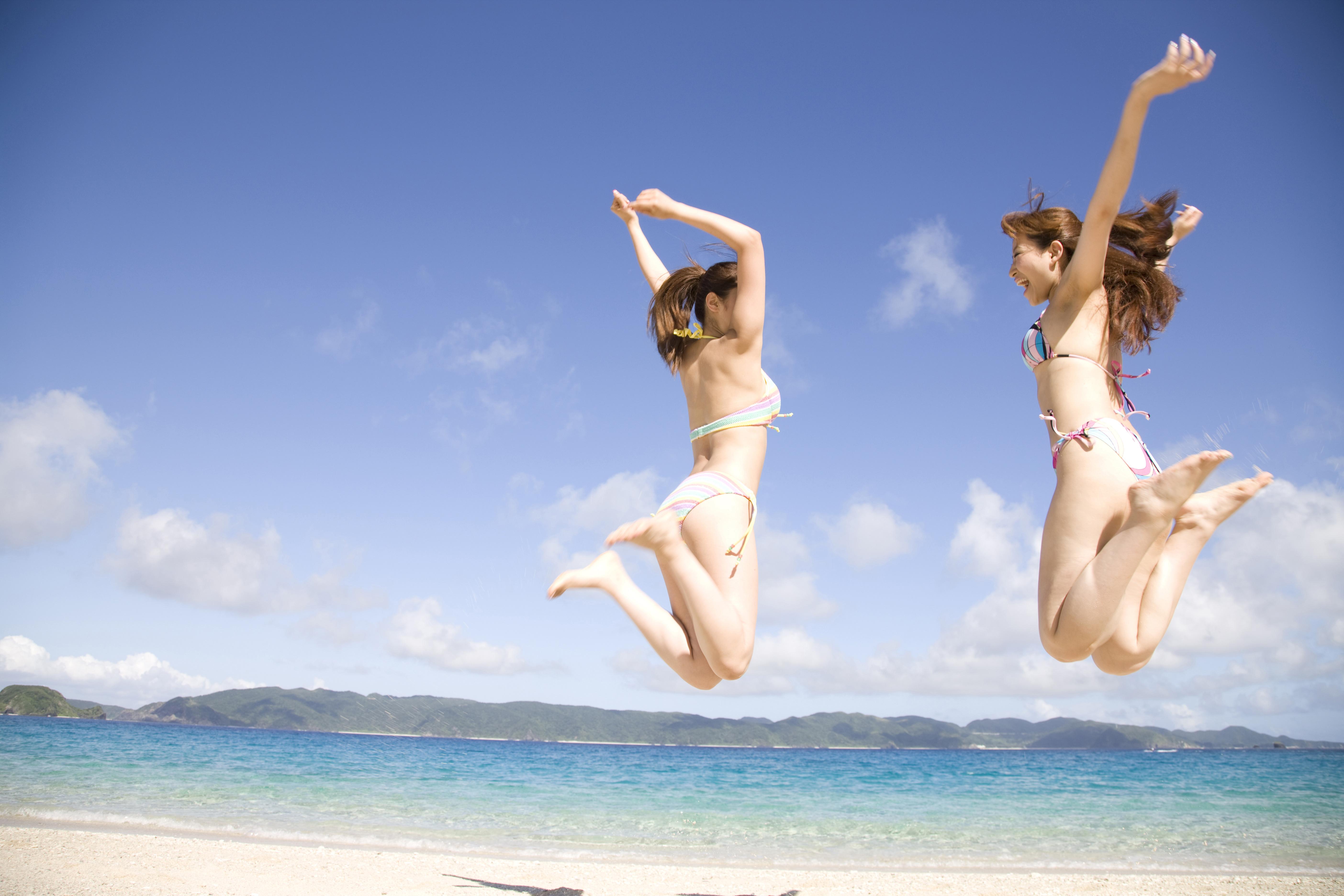 浜辺でジャンプする水着を着た2人の女性の後ろ
